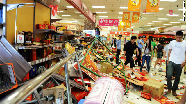 Security guards try to remove a group of Chinese protesters who ransacked Japan's JUSCO departmental store, in Qingdao.
