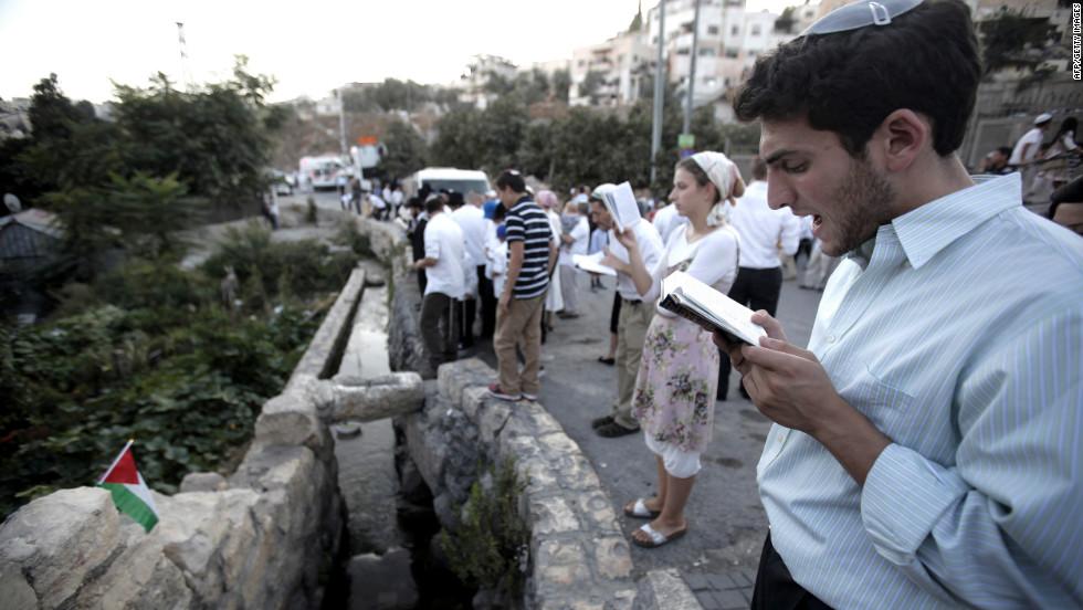 Israeli Jews recite the Tashlich prayer near a water source in the Arab east Jerusalem neighborhood of Silwan on Monday.