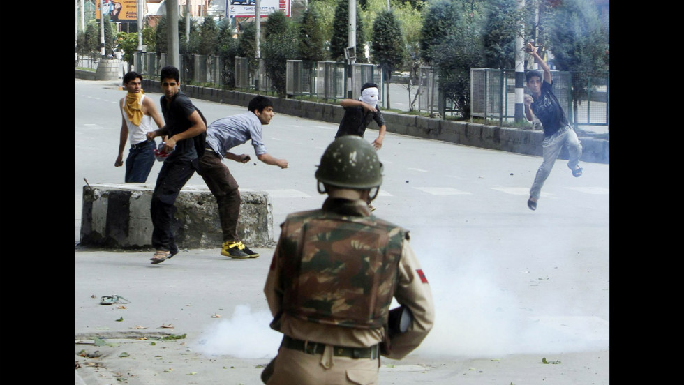 Kashmiri Muslims throw stones at Indian police during a protest on Tuesday in Srinagar.