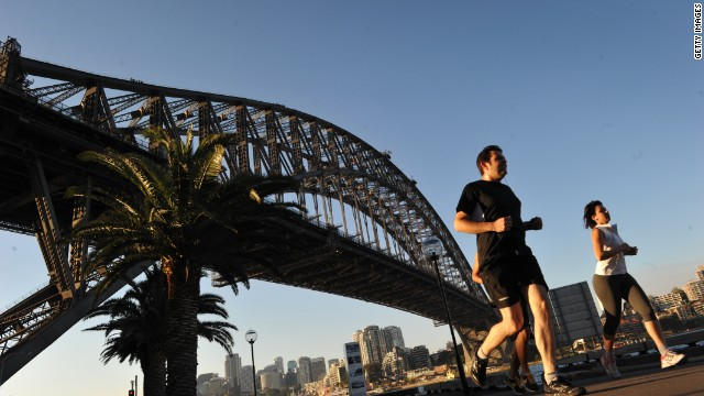 People jog along the Sydney Harbour with the Sydney Harbour bridge seen in the background on September 10, 2012. The iconic landmark is one of the top attractions in Sydney. AFP PHOTO/ROMEO GACAD (Photo credit should read ROMEO GACAD/AFP/GettyImages)
