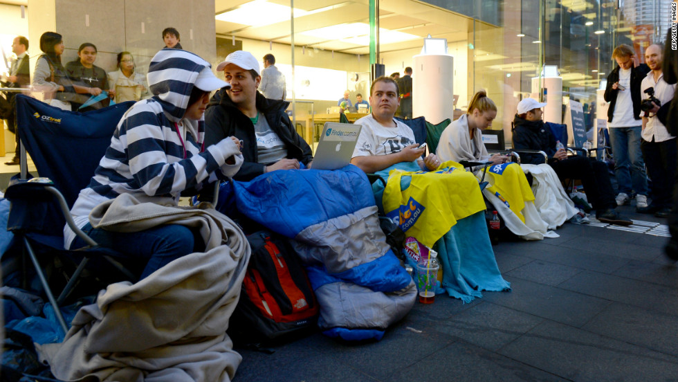 From New York to Tokyo, people are already lining up outside Apple stores to buy the iPhone 5, which goes on sale Friday. Here, people sit in a queue outside Apple's flagship store in Sydney on Thursday.