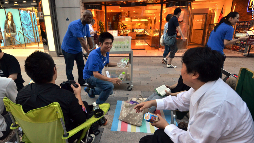 Apple store staff hand out free drinks and chocolate to Apple fans queuing on the sidewalk for the launch of Apple's new iPhone 5 in Tokyo.