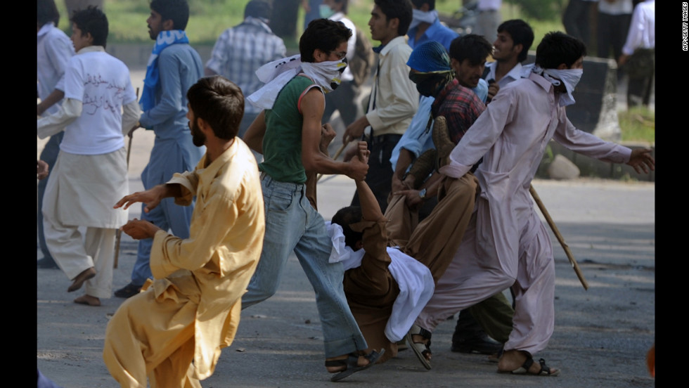 Pakistani demonstrators carry an injured person on Thursday.