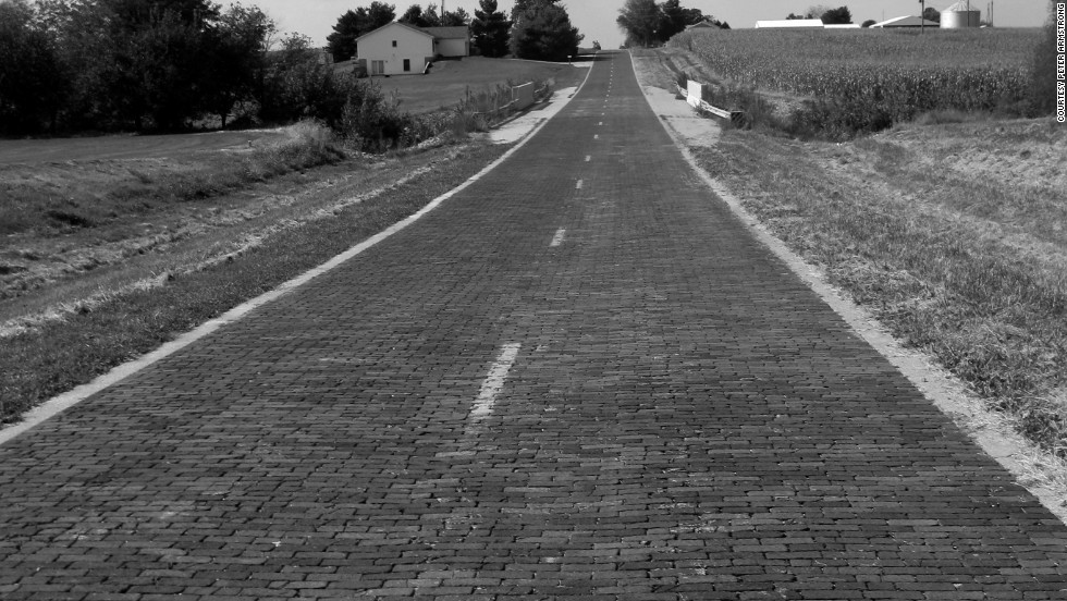 "The so-called ""most famous highway in the world,"" Route 66's surface varied from pavement to dirt to brick, shown here near Auburn, Illinois."