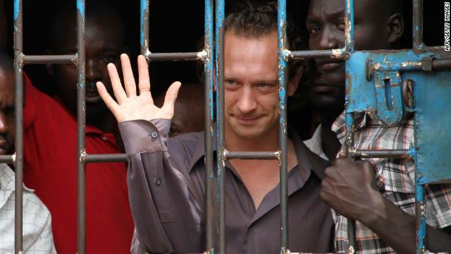 British theater producer David Cecil waves from a court cell in Kampala last week