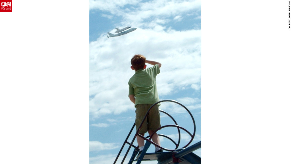 "Spencer Niegocki, 10, <a href=""http://ireport.cnn.com/docs/DOC-844391"">salutes Endeavour</a> from the top of a playground slide as the shuttle is flown over Tucson, Arizona, on Thursday, September 20. ""Years from now, he will be able to look back and say he saw the last shuttle get carried to its final home,"" said his father, Dann Niegocki. ""He may not understand it now, but we all participated in something impressive through the shuttle program."""