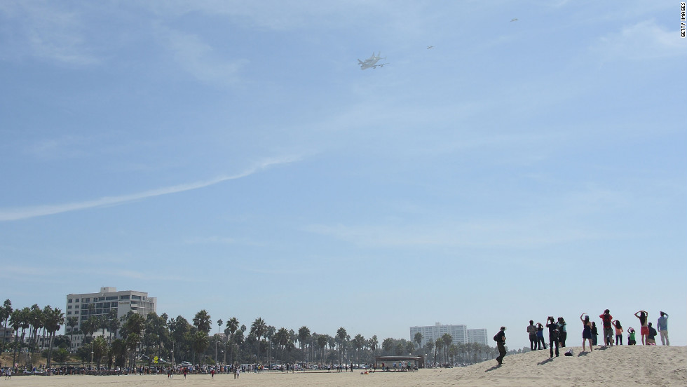 People at Santa Monica Beach watch the space shuttle arrive in Los Angeles on Friday.