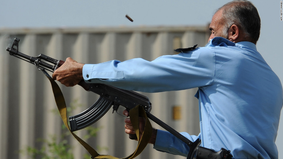 A Pakistani police officer fires an automatic weapon toward demonstrators during a protest Friday in Islamabad.
