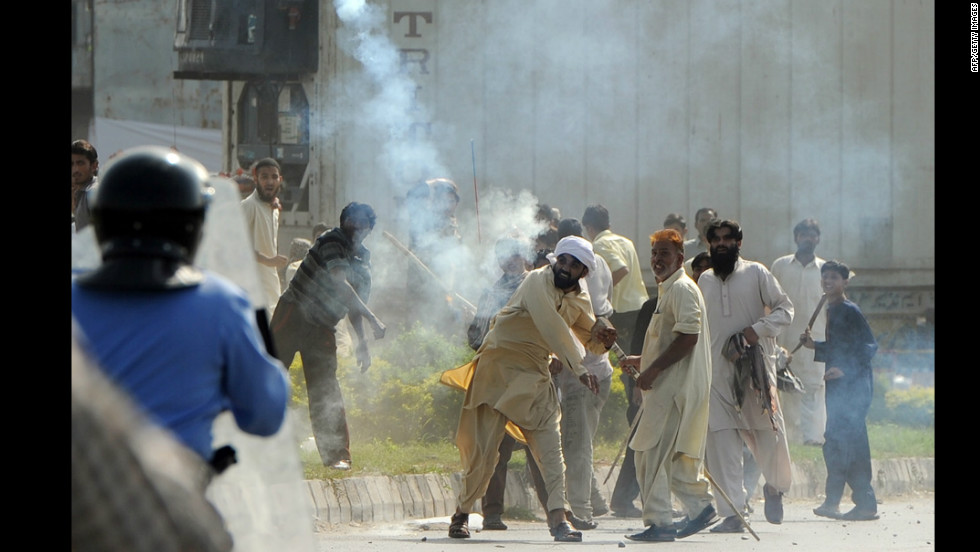 A Pakistani demonstrator throws a tear gas shell toward riot police during a protest against an anti-Islam film in Islamabad on Friday, September 21. Angry demonstrators set fire to two movie theaters in Pakistan's northwestern city of Peshawar as many braced for intensified protests Friday, officials said.