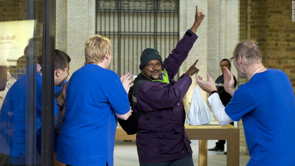 Apple Store employees applaud a customer after his new purchase.