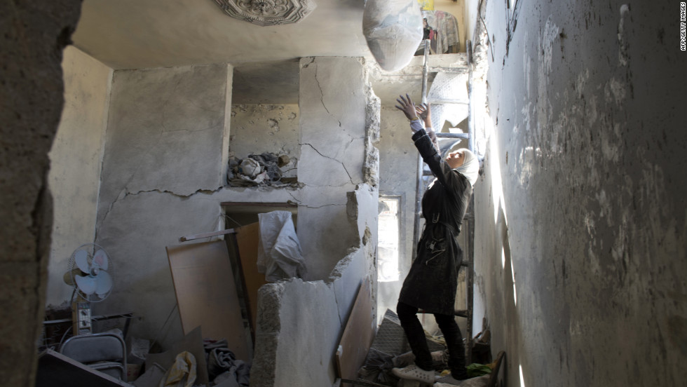 A Syrian woman prepares to grab a bag of belongings as she stands amid rubble at a house where a child was killed Friday.