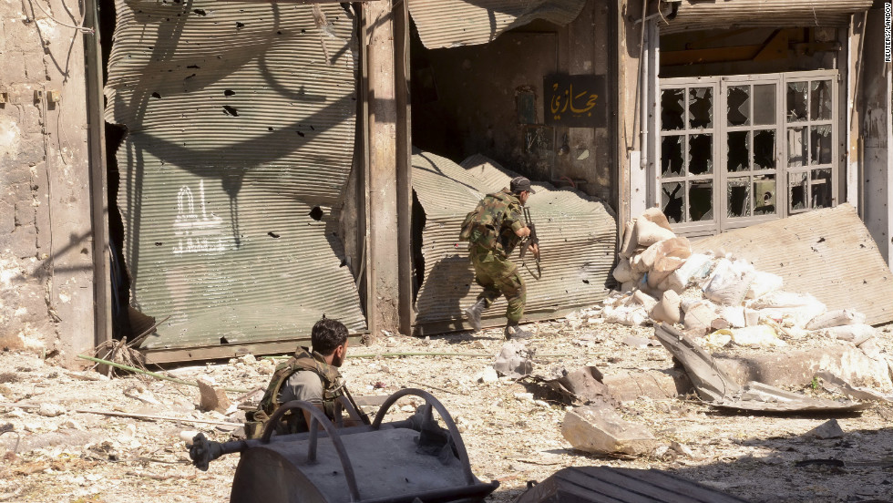 Syrian Army soldiers run in a damaged area in Aleppo on Sunday.