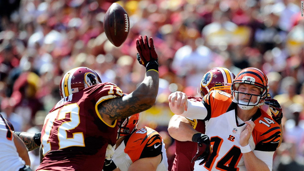 Bengals quarterback Andy Dalton is hit as he throws a pass. The Redskins' Rob Jackson would intercept and return it for a touchdown.