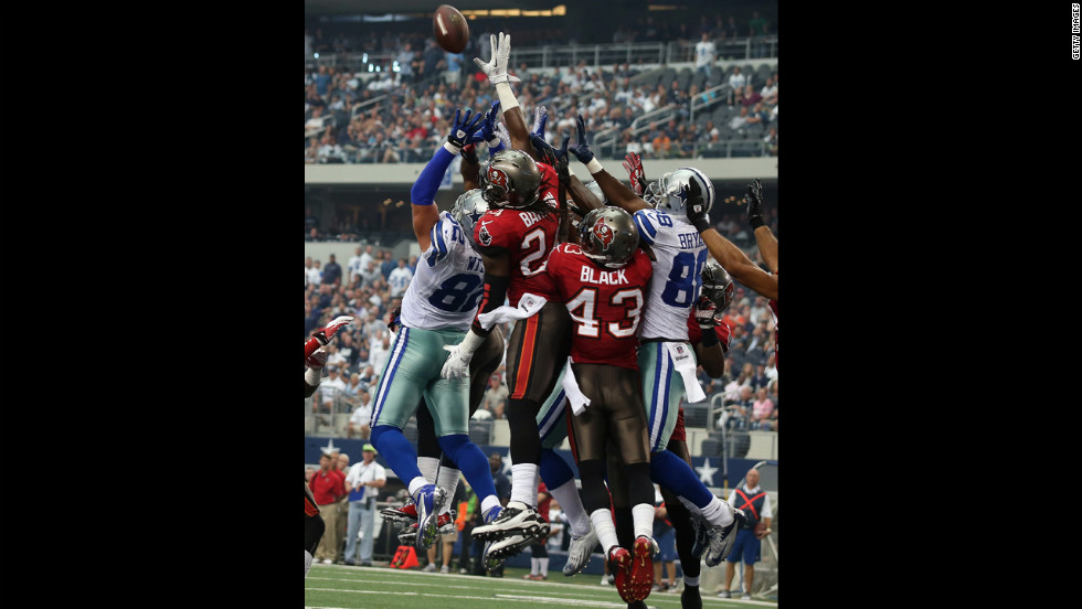 Cowboys and Buccaneers players jump for the ball in the endzone.