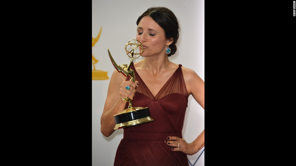 "Julia Louis-Dreyfus of ""Veep"" kisses her trophy for best lead actress in a comedy."