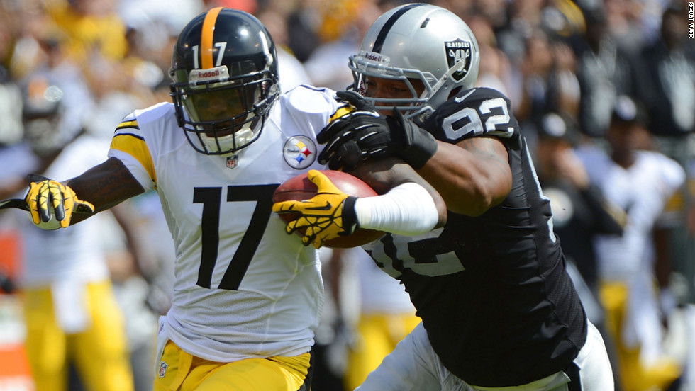Mike Wallace of the Steelers gets caught from behind by Richard Seymour of the Raiders.