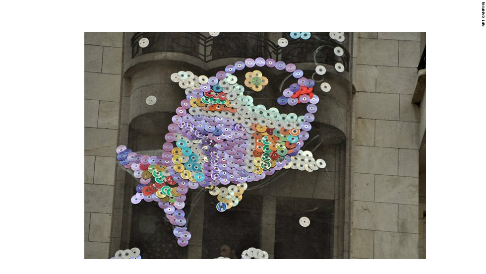 "A giant fish made from CDs and and DVDs on the wall of a building in central Aleppo. They were collected by Art Camping participants in April. The fish remains in place despite heavy fighting in the area. ""I think both sides like it,"" said Touma."