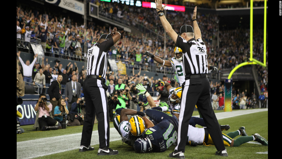 "On Twitter, this is being called the ""official photo"" of the replacement referee debacle. Two officials in the end zone gave contradictory signals: One signaled a touchdown and the other signaled a clock stoppage, indicating a change of possession and an interception."