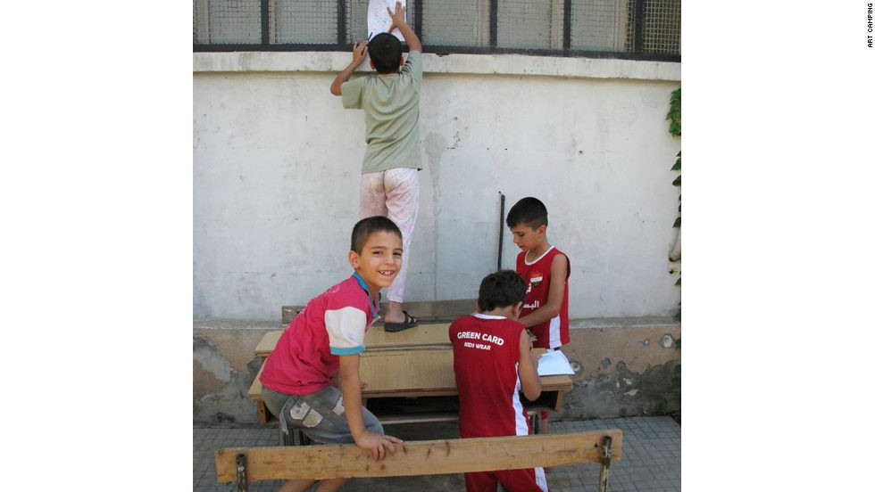 "Children taking pencil rubbings as part of a ""textures of the city"" project through Art Camping in Aleppo on August 13, a few days before fighting reached the city center."