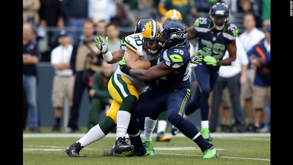 Green Bay's John Kuhn runs the ball against Danny Gorrer of Seattle.