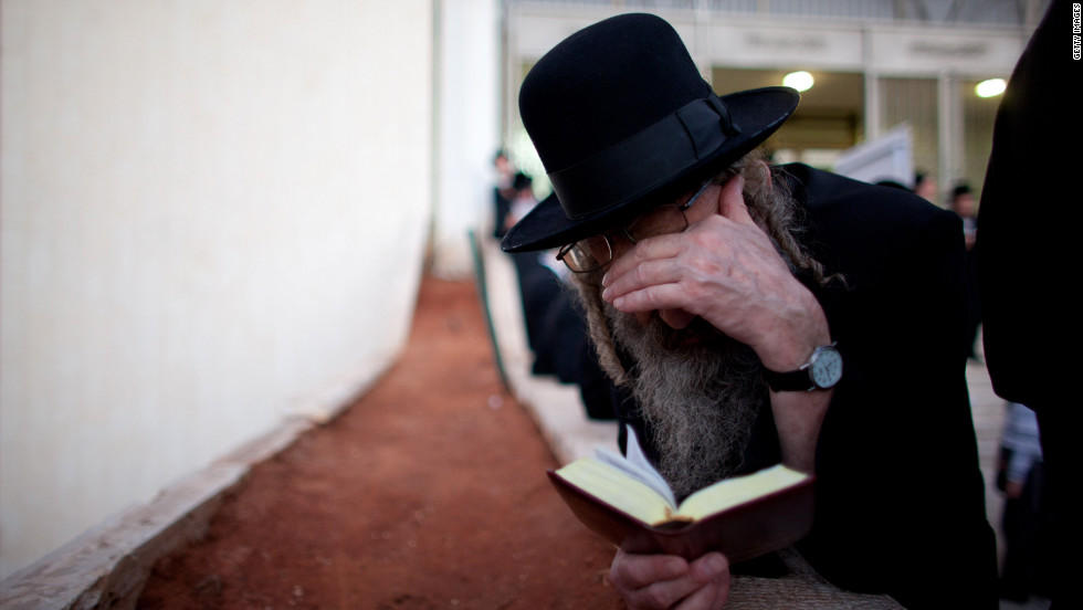 "A man prays as Ultra-Orthodox Jews perform the Tashlich ritual on Monday, September 24, in Bnei Brak, Israel. Tashlich, which means ""to cast away,"" is the practice by which Jews go to a flowing body of water and symbolically throw away their sins during the days of repentance between Rosh Hashanah and Yom Kippur."