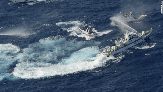 A Japan Coast Guard vessel, right, sprays water against Taiwanese fishing boats in the East China Sea.
