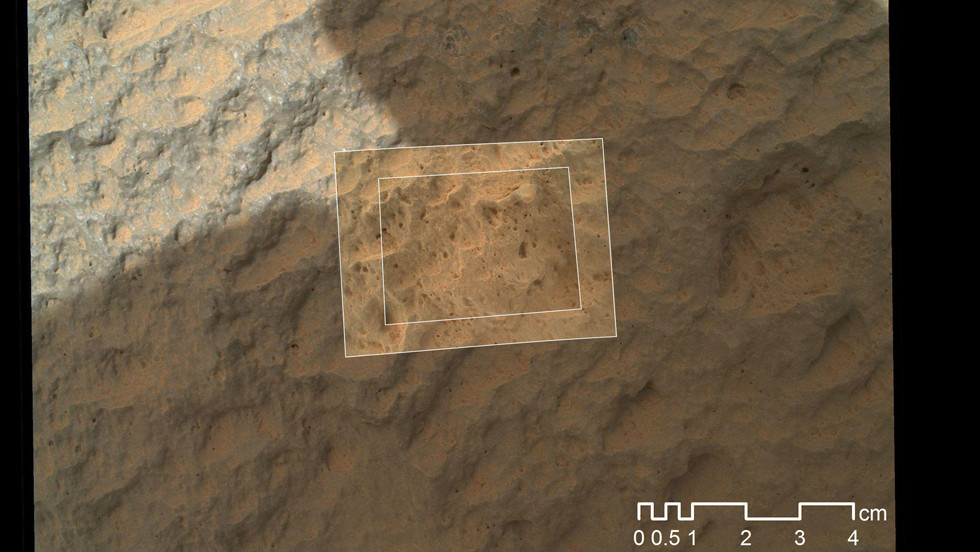 This image combines photographs taken by the rover's Mars Hand Lens Imager at three distances from the first Martian rock that NASA's Curiosity rover touched with its arm. The images reveal that the target rock has a relatively smooth, gray surface with some glinty facets reflecting sunlight and reddish dust collecting in recesses in the rock.