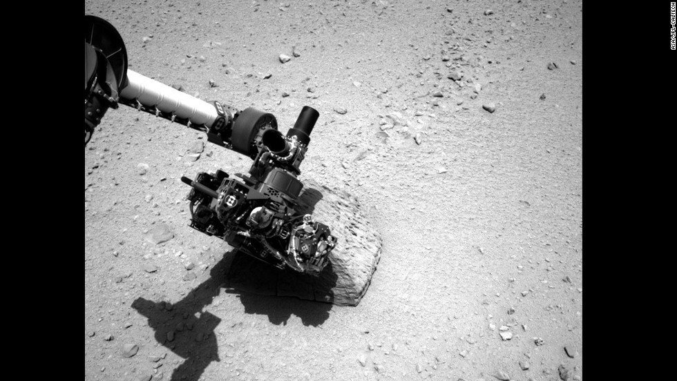 This image shows the robotic arm of NASA's Mars rover Curiosity with the first rock touched by an instrument on the arm. The photo was taken by the rover's right navigation camera.