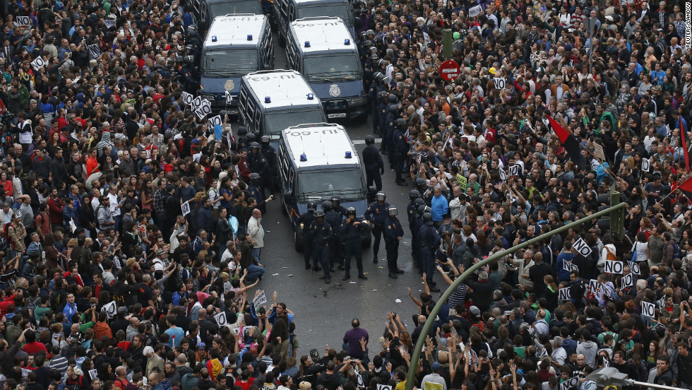 Protesters surround police vans near the Spanish Parliament in Madrid on Tuesday, September 25. Spain's unemployment is near 25%, and demonstrators -- fed up with anti-austerity measures -- accuse the government and opposition alike of trying to solve the country's financial woes on the backs of the people.
