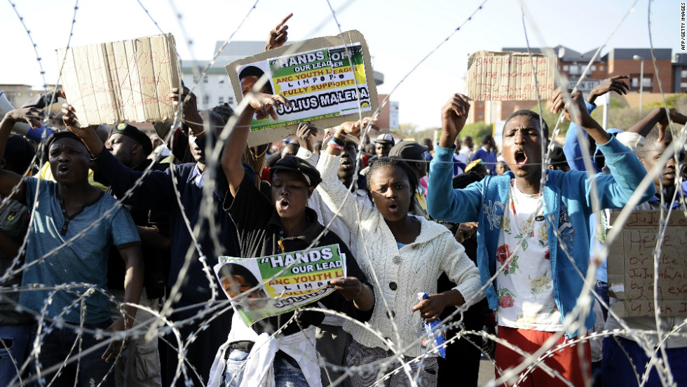 Demonstrators gather behind a razor wire outside the courthouse on September 26, singing songs in Malema's support. Some held an overnight vigil at a local hall amid heavy security presence that included riot police.