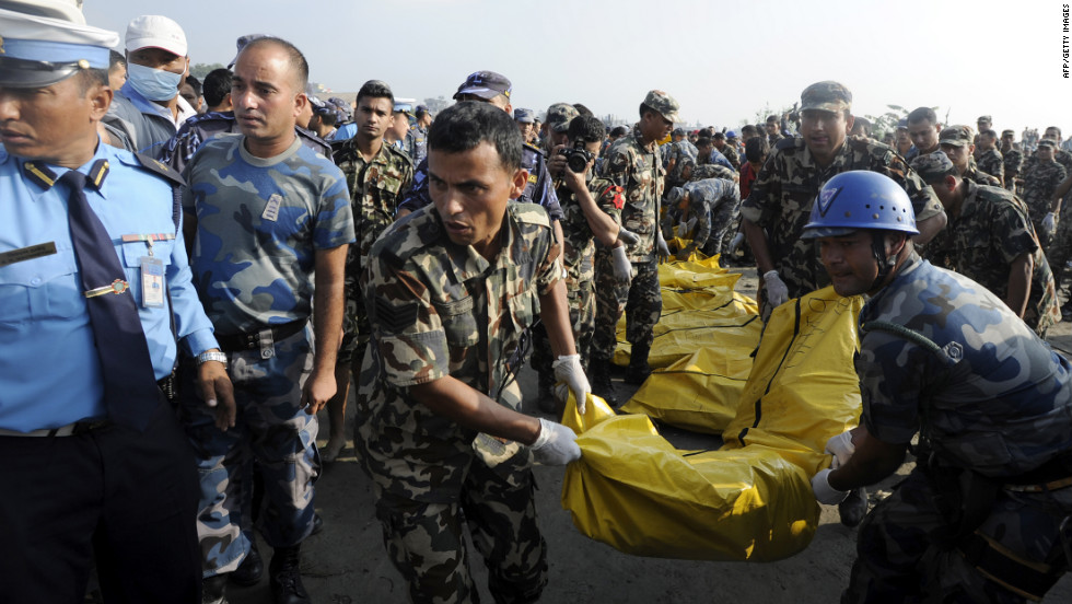 Members of a Nepalese rescue team remove bodies found in the wreckage. The UK Foreign Office confirmed that seven Britons were on the flight, and China's Ministry of Foreign Affairs also said five Chinese died.