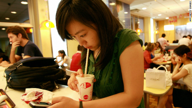 A young woman uses her mobile phone at a fastfood outlet in Beijing, on September 5 2007.