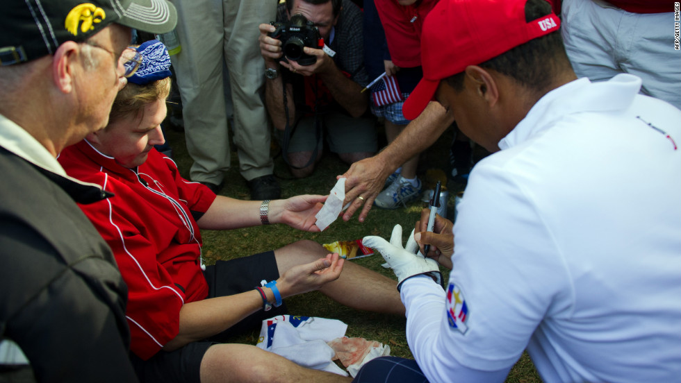 Tiger Woods signs his glove for a fan who was struck in the head during his drive off the seveth tee on Friday.