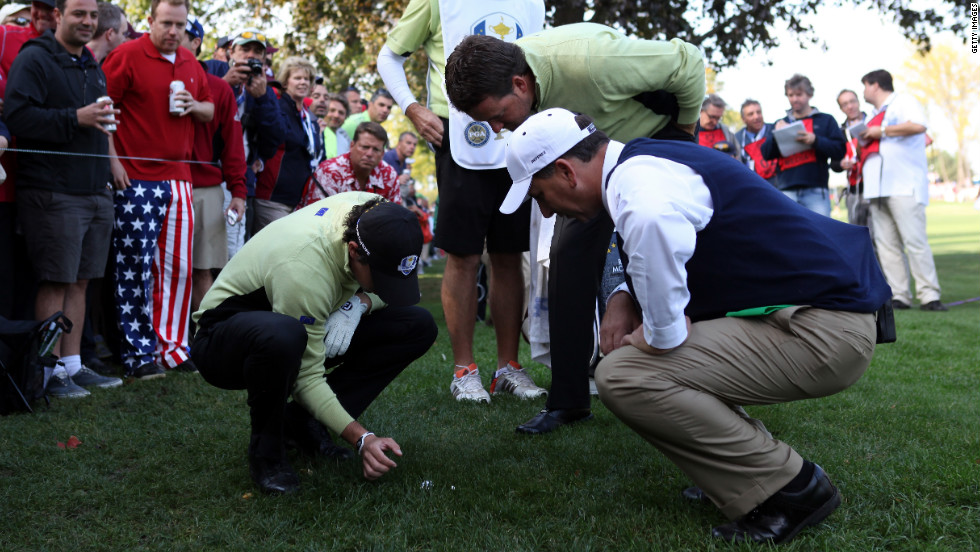 Rory McIlroy and Graeme McDowell of Europe get a ruling on their ball on the 18th hole Friday.