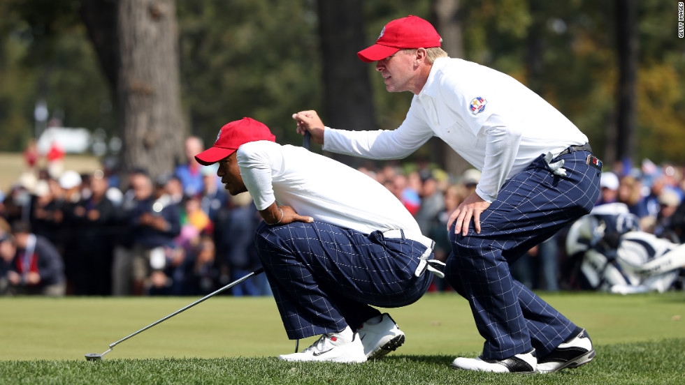 Tiger Woods and Steve Stricker line up a putt during the morning foursome matches on Friday.