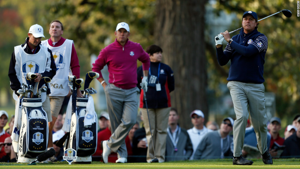 American Phil Mickelson watches his tee shot on the fourth hole as Lee Westwood of Europe looks on.