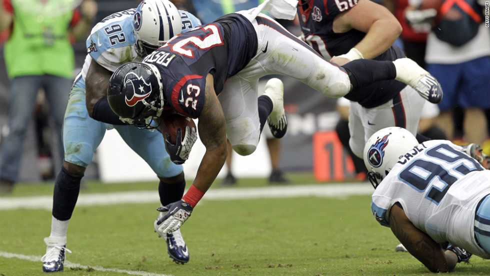 Arian Foster of the Houston Texans leaps over Jurrell Casey, No. 99 of the Tennessee Titans, as he is tackled by Will Witherspoon, No. 92, at Reliant Arena in Houston on Sunday.