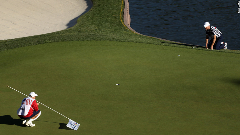 Jim Furyk of the United States lines up a putt with his caddie, Mike Cowan, on the 17th green.