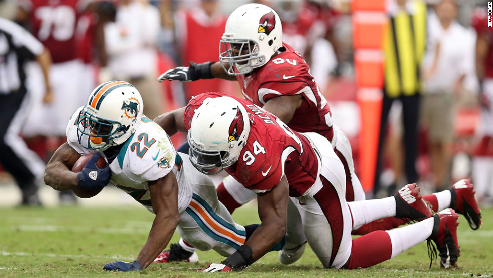 Reggie Bush of the Miami Dolphins is tackled in the backfield Sunday by No. 94 Sam Acho of the Arizona Cardinals.