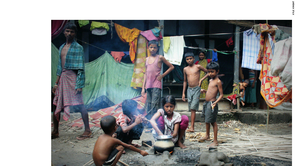 Children who live in a relief camp in a school in Chirang district cook food in the courtyard.