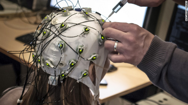 A researcher makes an adjustment to a cap with electrodes at the Neuroscience Research Center in Lyon, France.