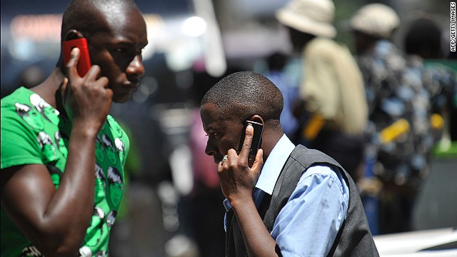 People walk while speaking on the phone in Nairobi, Kenya on October 1, 2012.