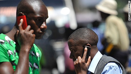 People walk while speaking on the phone on October 1,2012 in Nairobi, as Kenya confirmed a switch-off of counterfeit mobiles will take place at the end of the month.The mobile networks will be forbidden from activating new 'fake' devices bought after October 1. Government officials said the move was designed to protect consumers from hazardous materials and to safeguard mobile payment systems and prevention of crime. The government said three million users were using counterfeit handsets as of June. AFP PHOTO / SIMON MAINA (Photo credit should read SIMON MAINA/AFP/GettyImages)