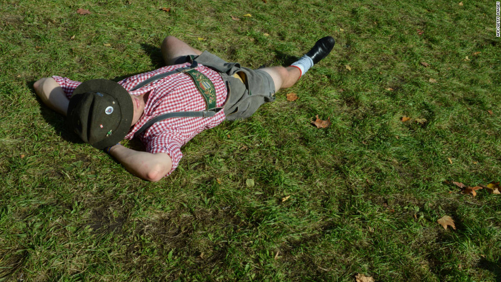 An Oktoberfest visitor has a rest on the lawn at the Theresienwiese.
