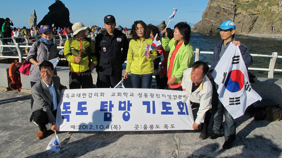 "A group of tourists from South Korea arrives on the islands on a ferry carrying flags. Kevin Kim, 40, says, ""I'm a native of Korea and an American citizen but in my blood I'm Korean... I feel so great to be here... It really makes me upset when Japan claims this island, it's absurd and it should not be tolerated."""