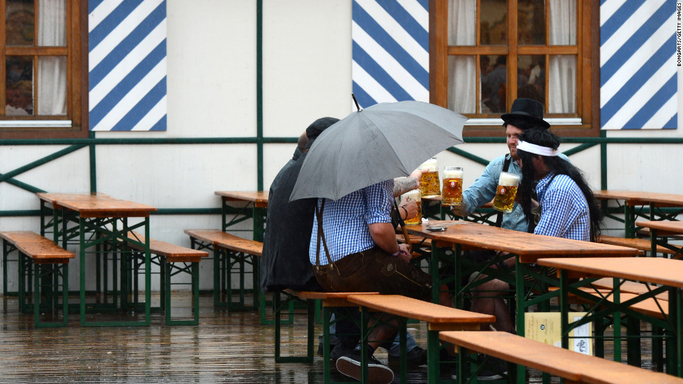 Visitors drink beer while rain falls on the Oktoberfest festival fairground on Sunday.
