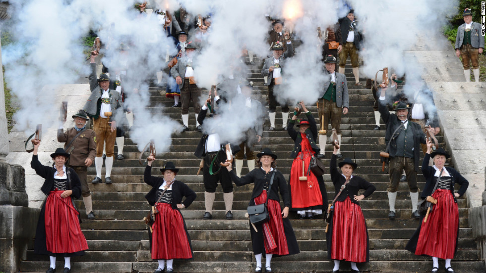 People in traditional Bavarian garb fire a salute Sunday on the steps of the Bavaria monument.