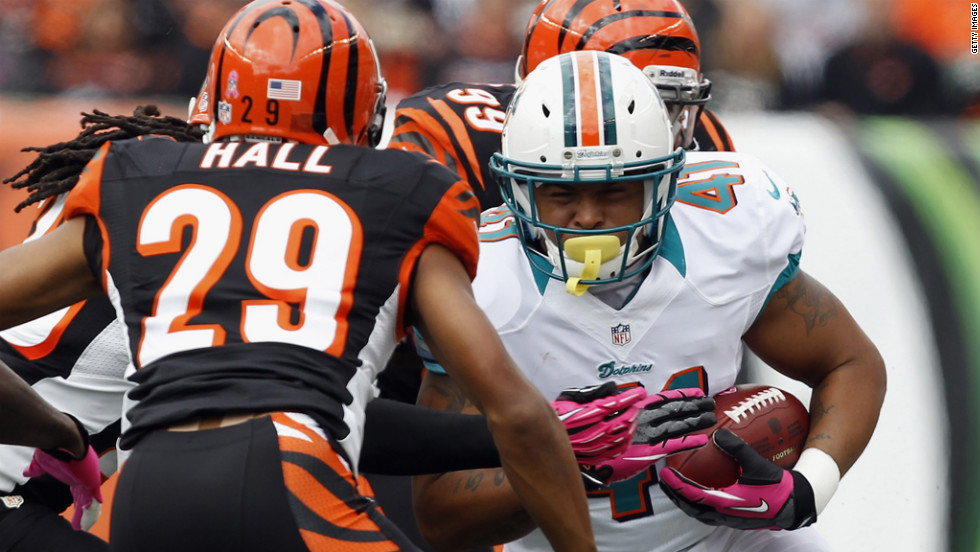 Jorvorskie Lane of the Dolphins tries to break tackles from Bengals defenders Leon Hall, No. 29, and Manny Lawson, No. 99.