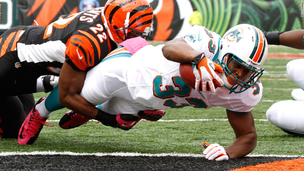 Daniel Thomas of the Dolphins dives into the end zone to score a touchdown against the Bengals.