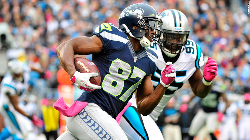 Ben Obomanu of the Seahawks is chased by Alan Branch of the Panthers as he turns upfield on a reverse.